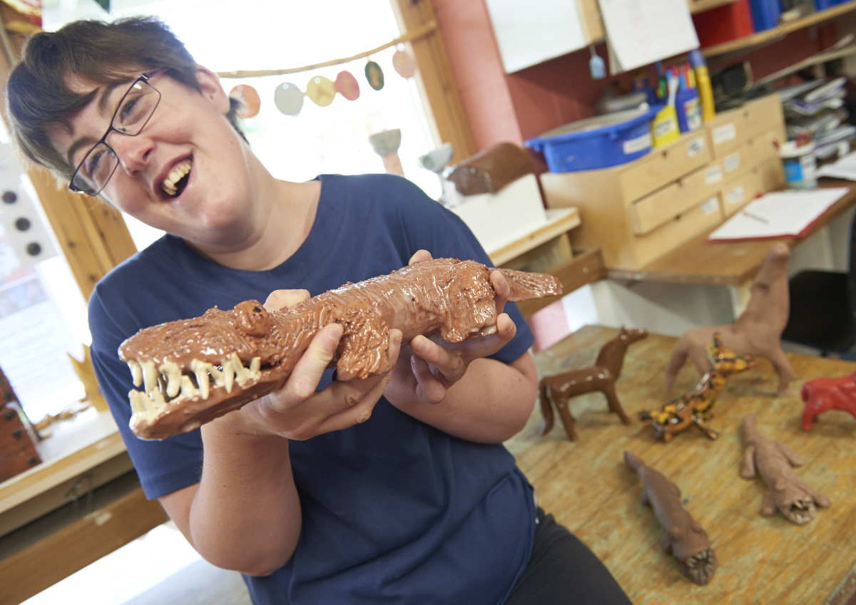 Art Maker Holding Up A Crocodile Made From Clay In The Pottery Workshop At Our Arts
