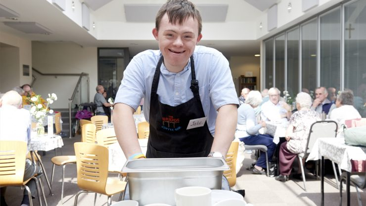 Student clearing tables as part of an employability work placement at a local cafe