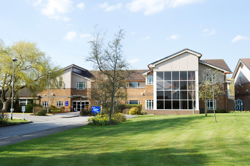 View of the front of Henshaws Specialist College with wide expanse of lawn at the front leading up to the main entrance. Visitors can explore the campus when you book a College visit.