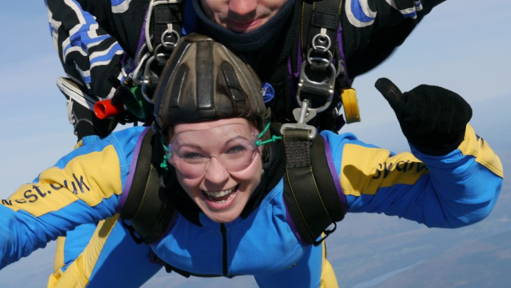 Image of Susan during her skydive for Henshaws, smiling and giving a thumbs up to the camera.