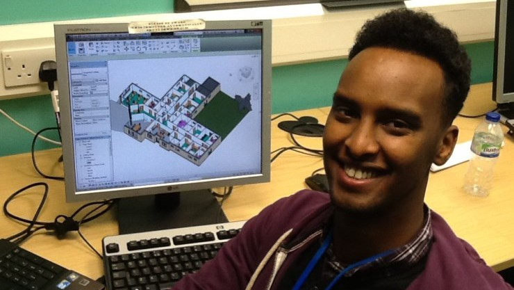Photo of Abdi, one of our Skillstep graduates, sitting by his desk at his new job at an architecture firm and smiling.