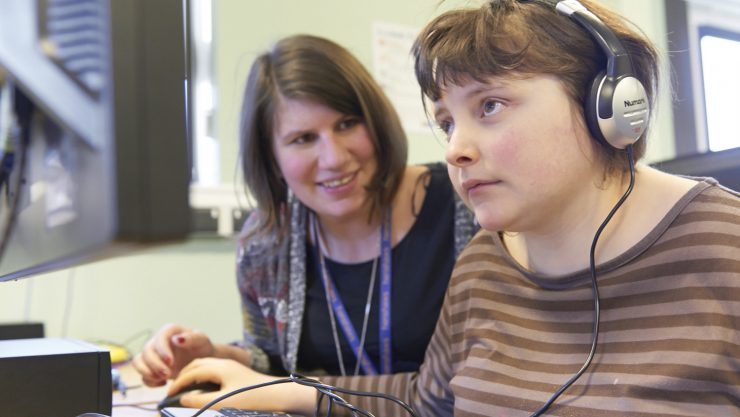 Photo of student Tessa wearing headphons and using a computer, next to a College member of staff.