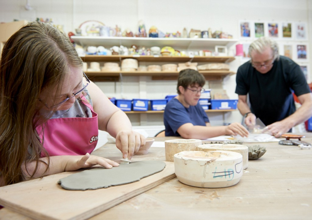 Art Makers creating clay bowls by stamping individual shapes from clay in our pottery creative workshop
