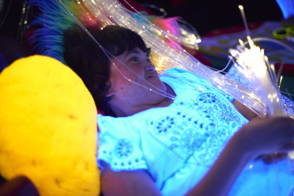 Art Maker enjoying a session with the fibre optics and glow in the dark cushions in our multisensory workshop