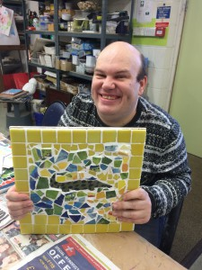Art Maker Wesley in the art studio holding up a mosaic he made which features a crocodile surrounded by yellow, blue and green tiles