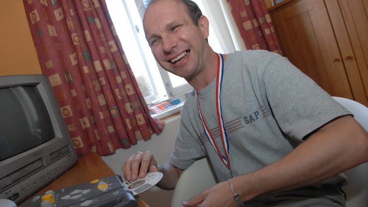 picture of service user smiling and putting in a DVD