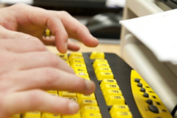 Hands using a high contrast keyboard with yellow keys