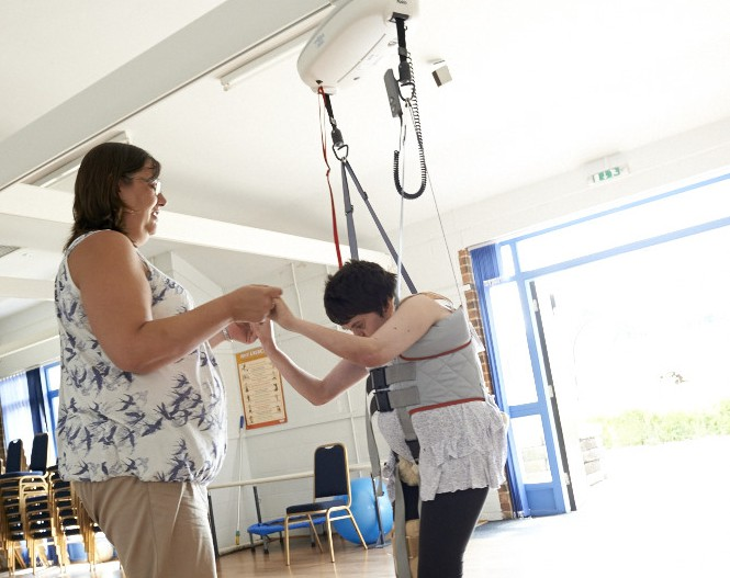 Art maker using a hoist to dance in the fitness workshop