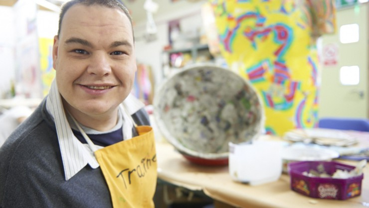 An Art Maker smiling with a colourful background in our paper workshop as he shares his experience as part of our stories from Henshaws Arts & Crafts