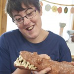 Art Maker Sally holds up a ceramic crocodile in our pottery workshop for people with disabilities