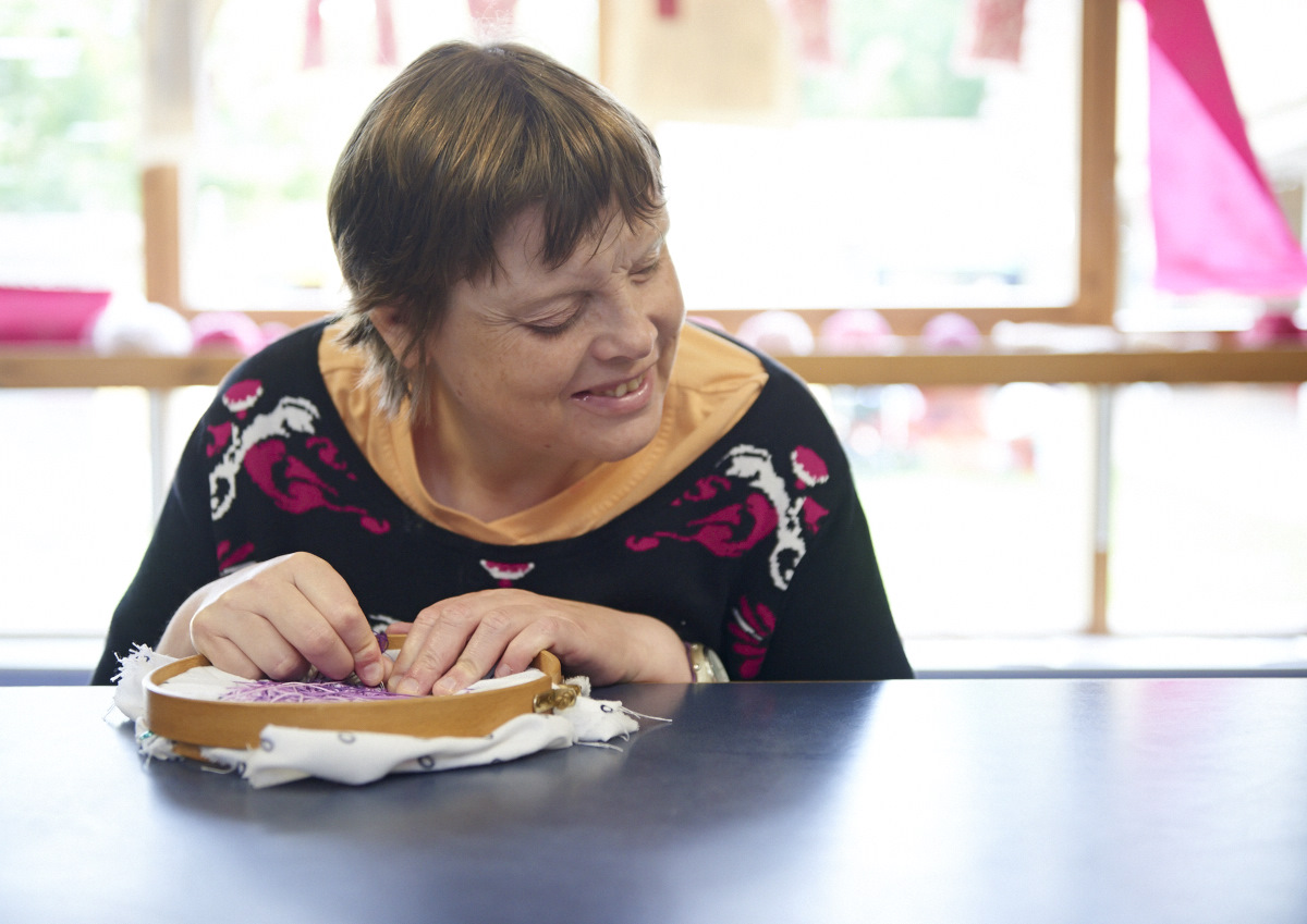 Art Maker creating an embroidery using an embroidery hoop and purple thread in one of our textiles creative workshops for people with disabilities