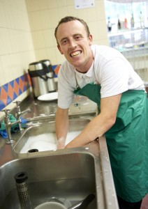 Art Maker Alex washing up in the sink in the arts & crafts centre cafe workshop