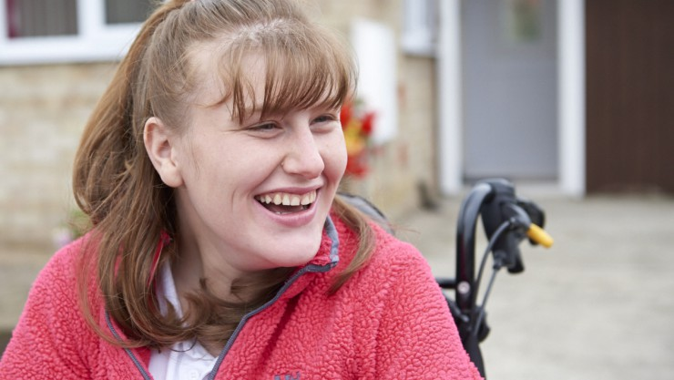 Close up image of Karina sitting in her wheelchair and smiling. Read Karina's story to hear how we are supporting young people living with disability to go beyond expectations
