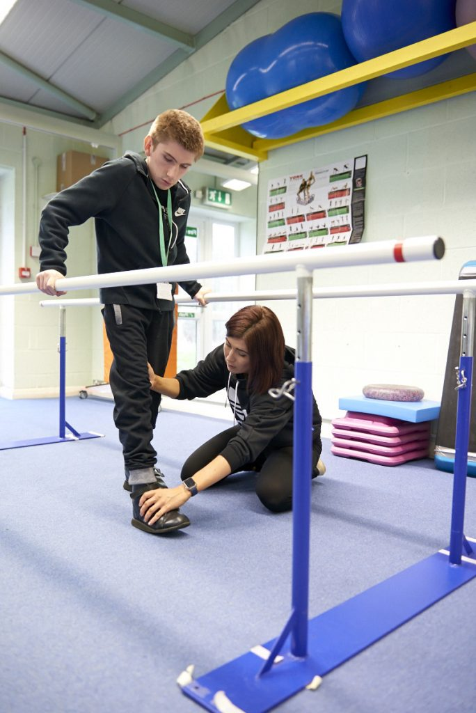 Student taking part in physiotherapy session using the parallel bars