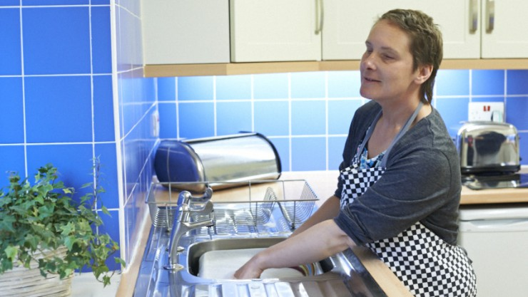 Image of Housing and Support resident Sam, standing in her kitchen and washing up in the sink.