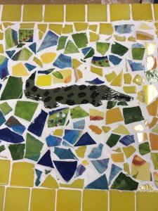Brightly coloured mosaic made in our art studio featuring a crocodile made from yellow, blue and green tiles