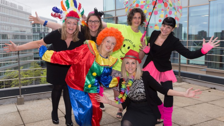 Image of staff from JMW wearing bright clothes in front of their office for Henshaws Bright for Sight