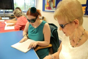 Kim and service user Wendy in a braille class