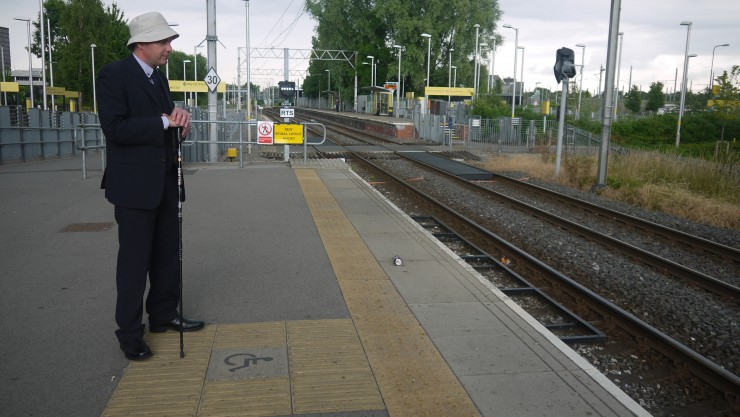 Photo of one of our Trustees, Andrew Rose, waiting at the tram stop.