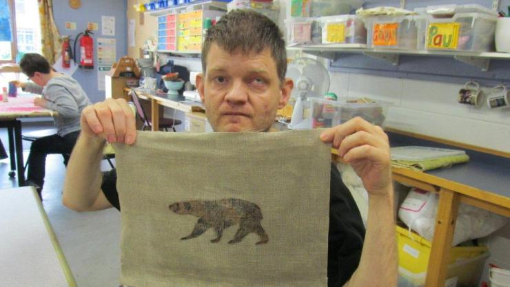 Paul holds up his printed textile of a bear