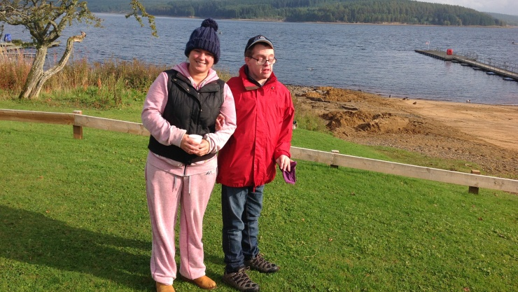 Gentleman and Support worker, standing by lake wearing outdoor clothing