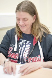 Image of Service user Janet reading braille