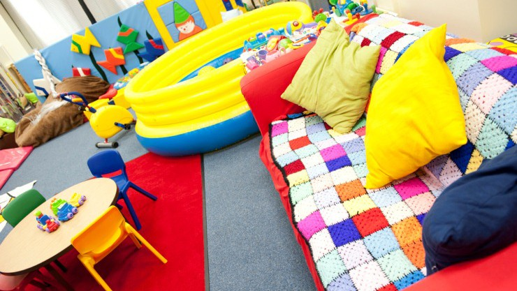 A brightly coloured soft play area - with blankets, inflatable toys, and soft chairs.
