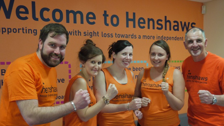 Henshaws staff, who ran for the Great Manchester Run 2015, wearing their Henshaws t-shirts and making a cheering gesture.