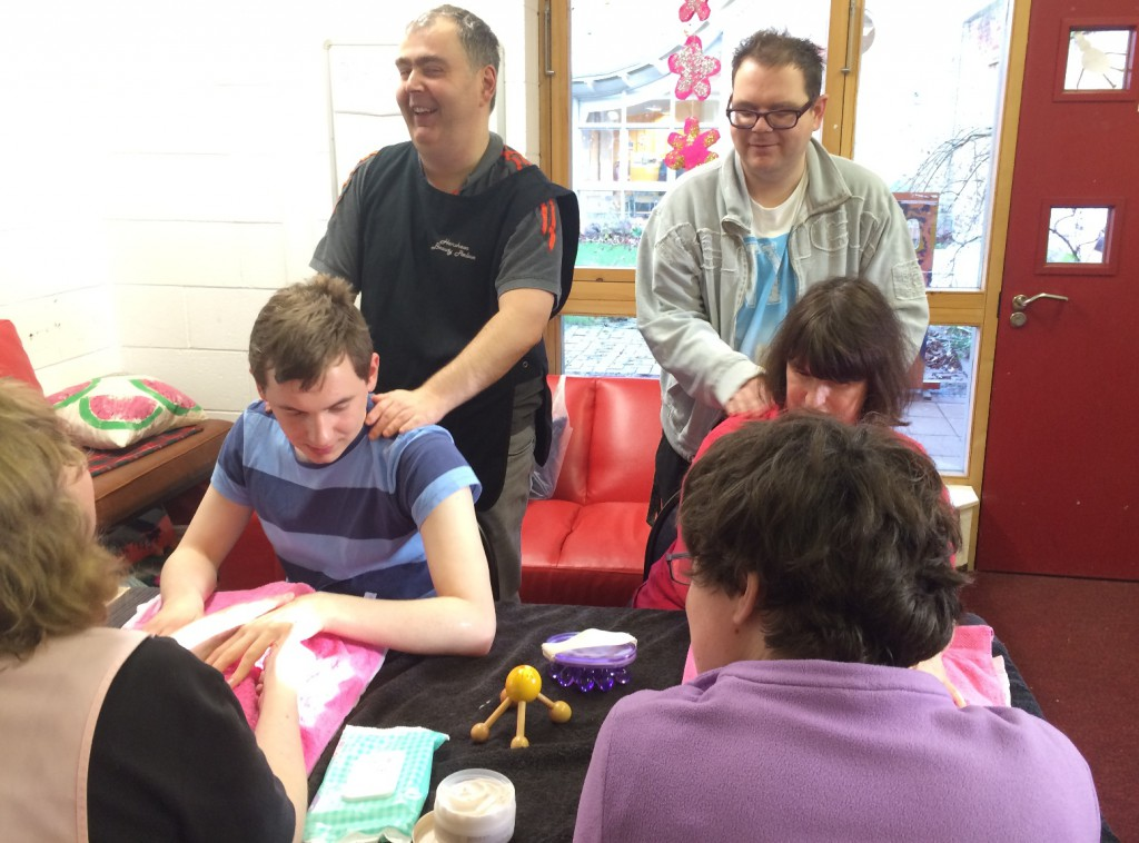 Art makers in our treatment and wellbeing workshop offering back and hand massages to other Art Makers