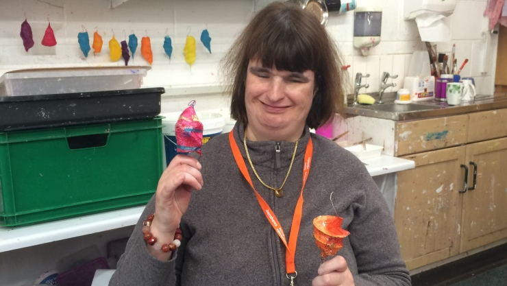 Art Maker Vicky with two of her brightly coloured lanterns which she made in our paper workshop for people with disabilities