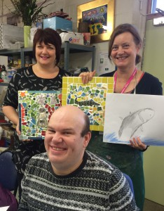 Art Maker Wesley with staff and volunteer holding up soem of his work which includes a pencil drawing of a shark and crocodile mosaic