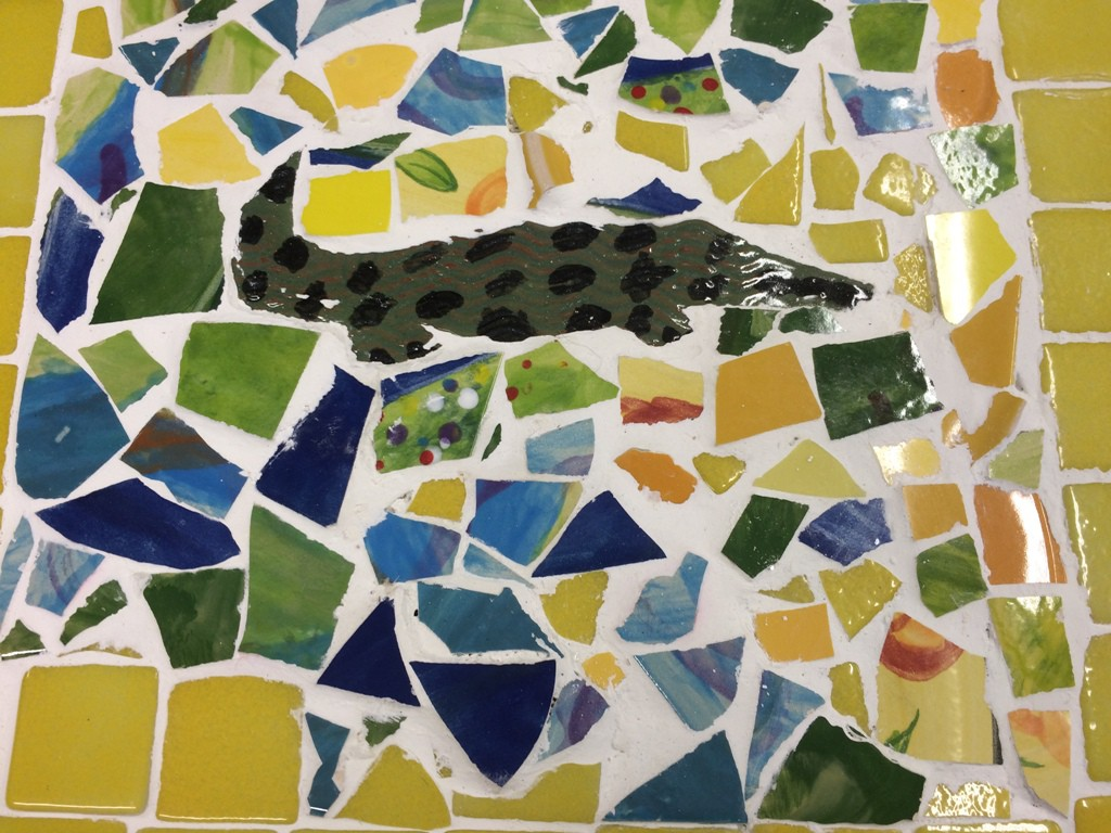 Brightly coloured crocodile mosaic made by an Art Maker in our art studio using green, red, yellow and blue tiles