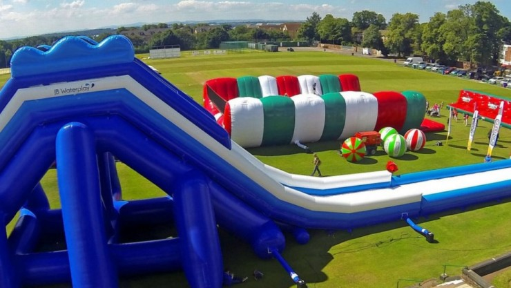Image of the Gung-Ho obstacle course; with a huge inflatable slide in central focus.