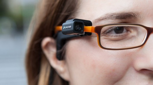 Close-up image of a woman modelling the OrCam glasses.
