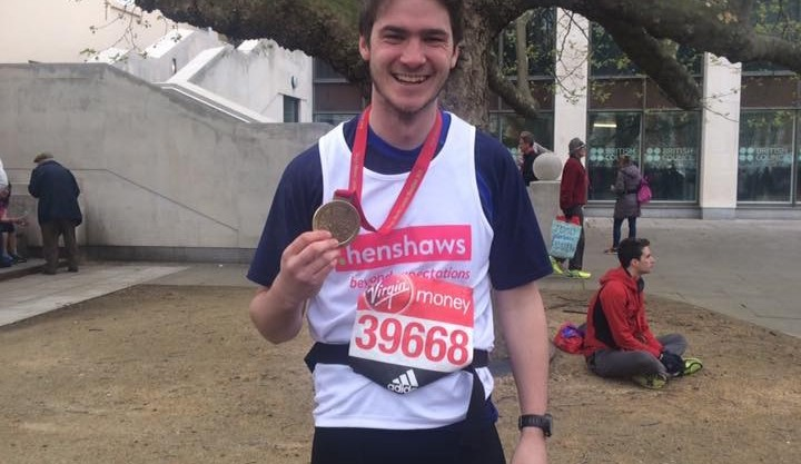 Runner Dan smiling after his marathon and holding up his medal