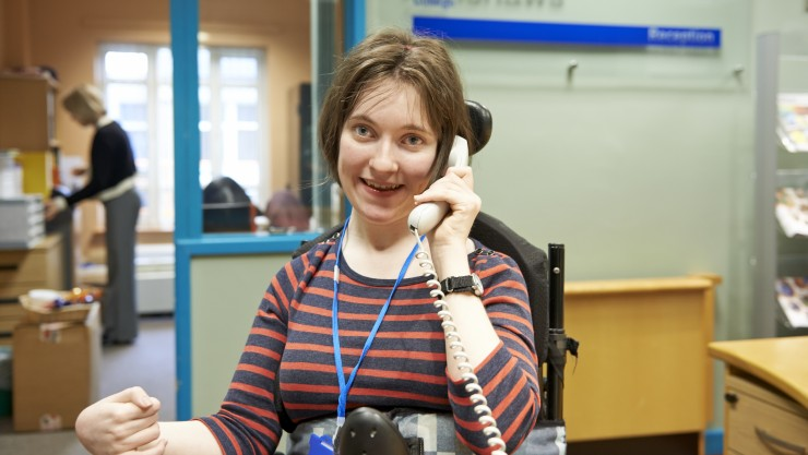 Student Rachael answering the telephone whilst on work placement at college