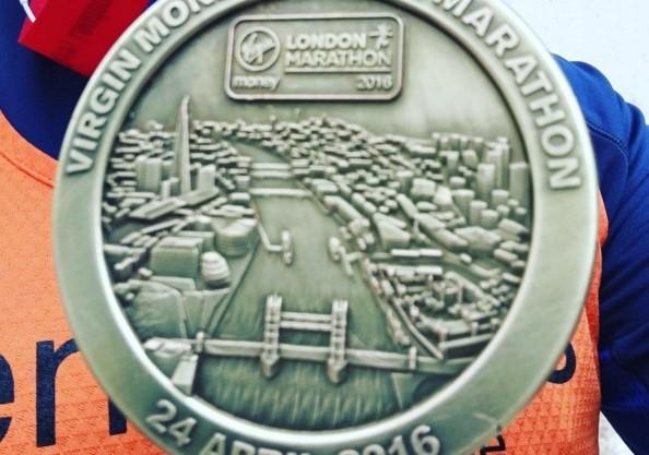 Runner Tom holding up his Marathon medal