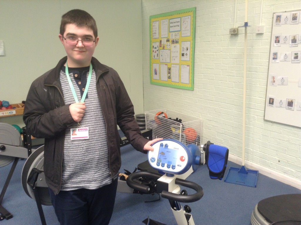 Student Tom standing next to Motomed machine in the college gym