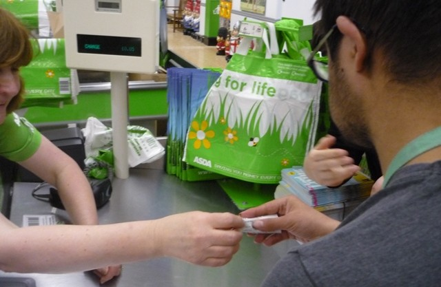 Cashier hands over receipt to student shopping in asda