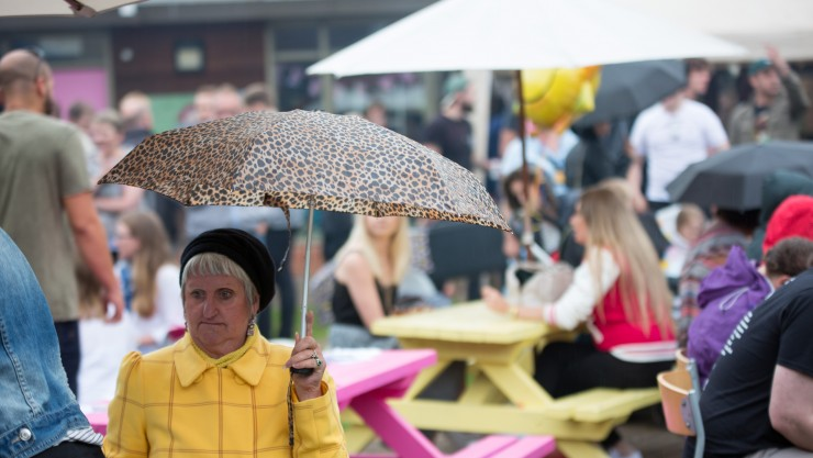 Lady with umbrella shelters from the rain at Bed Fest music festival