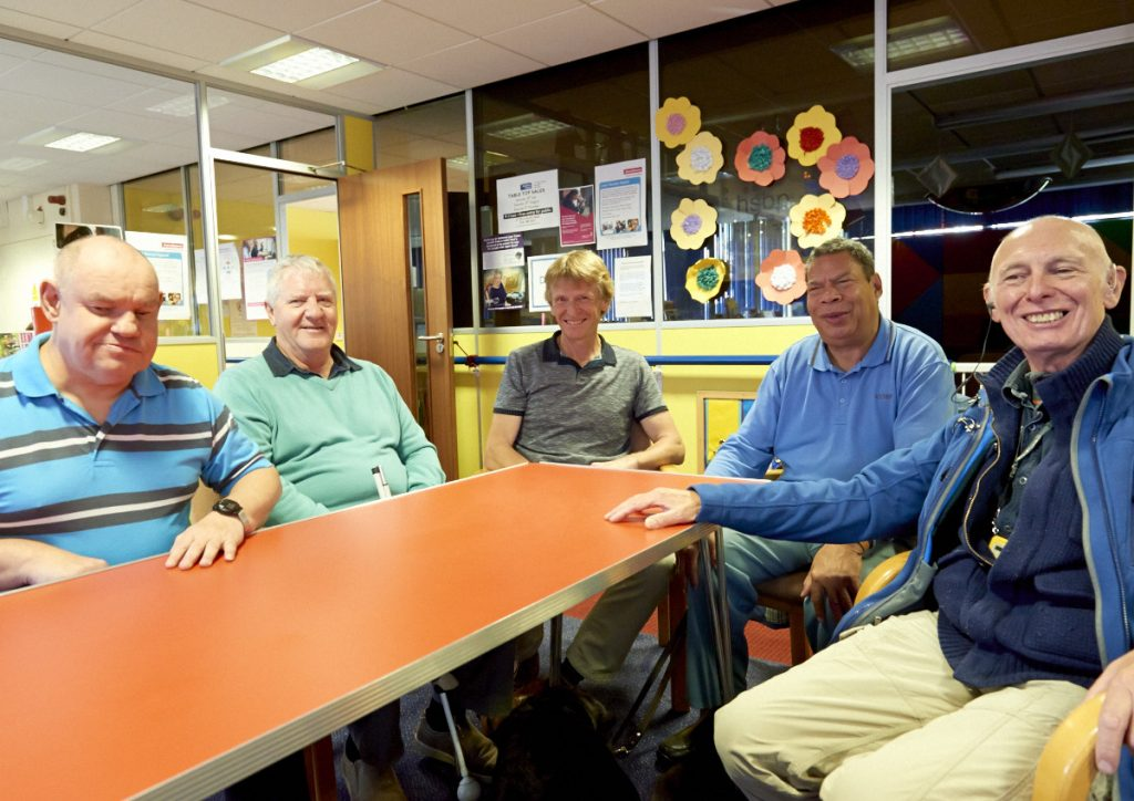 Five men sat round the table at the Manchester centre, smiling at the camera