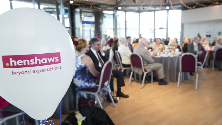 Image of the room at Henshaws awards 2016 - a balloon with the Henshaws logo is at the forefront, and everything else is blurred in the distance