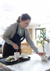 Student clears tables on cafe work placement