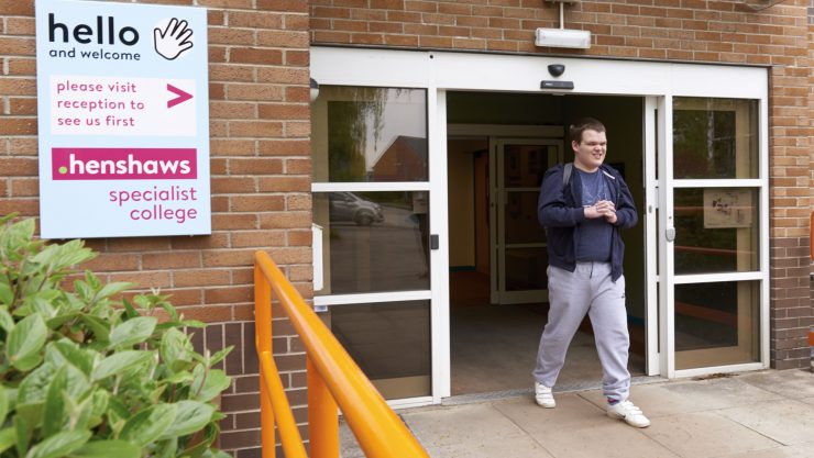 Student walking through main doors to leave college