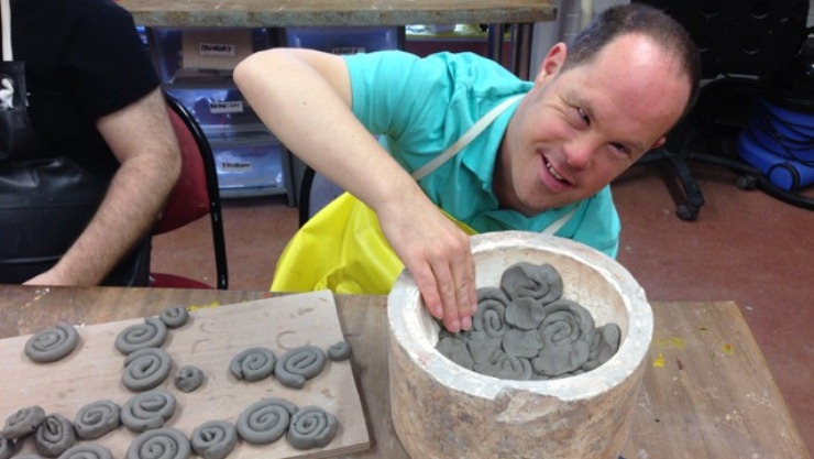 Art Maker pressing clay into globe mould
