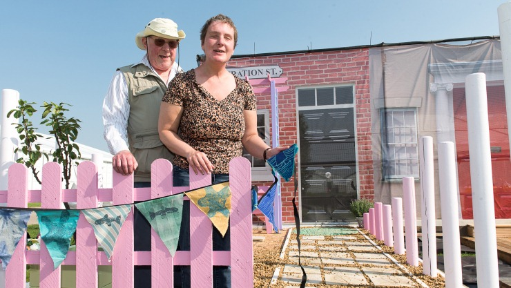 Art Maker and volunteer stood by a pale pink fence in the show garden