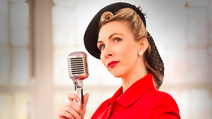 Lady dress in 1940s red suit and black hat, blond hair in victory roll, holding old fashioned radio microphone