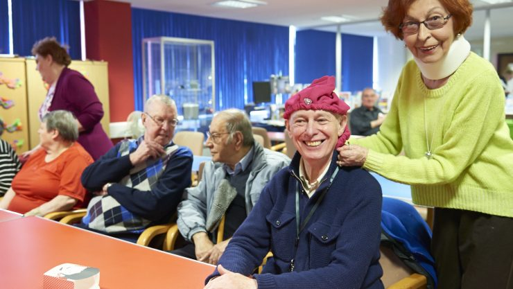 Marion putting a tea cosy on her friend's head at a social group