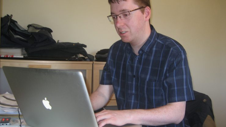 Image of volunteer Tom sat at his desk, using an Apple laptop.