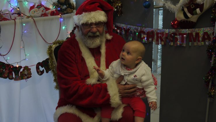 A baby sitting on Santa's lap, looking up at him in wonder at the Children & Families Christmas Party 2015.